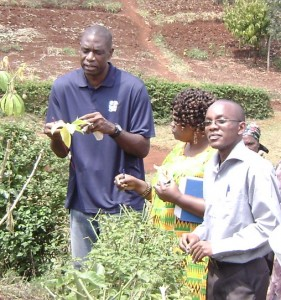 Mutombo (pictured at far left), the global ambassador of the NBA, represented Cindy McCain at a visit to 3rd year scholar Michael Murigi's (pictured at right) cassava project in Maragua Division.